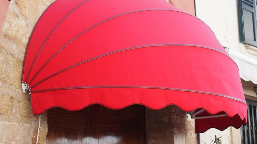 Rote halbrunde Markise an einer Häuserwand. Die Markise ist ausgeklappt