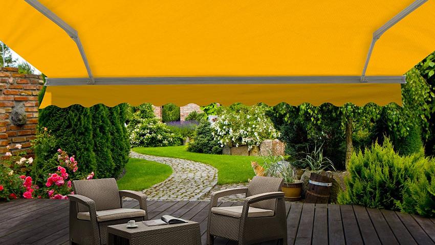 Gelbe markise die sich über Rattan-Gartenmöbel ausstreckt und diese beschützt