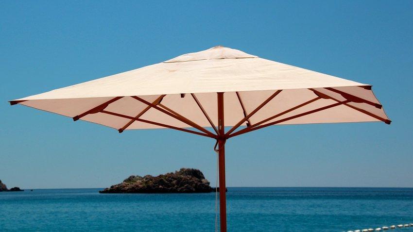 Beig-farbener Sonnenschirm vor dem Meer aufgespannt