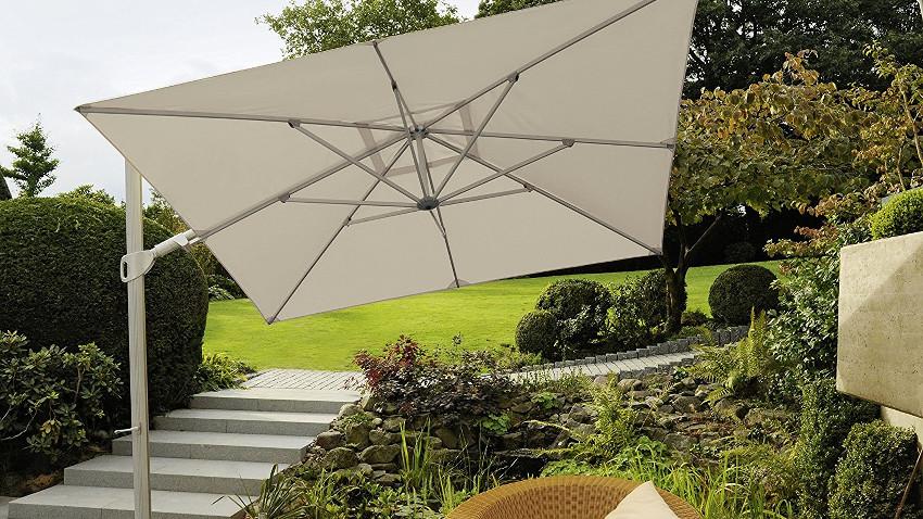 weißer Ampelsonnenschirm steht aufgespannt in einem Garten