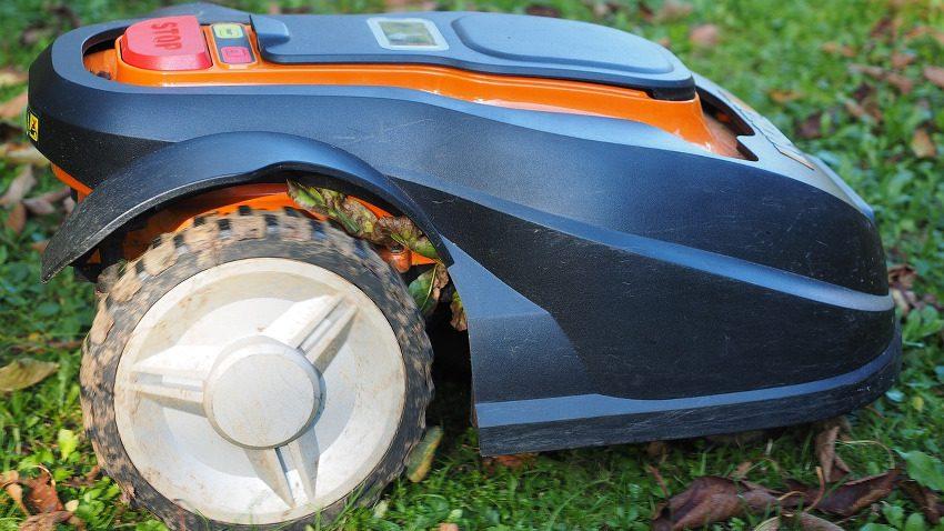 orang-blauer Rasen-Roboter beim Rasen Mähen. Der Rasenmäher ist von der Seite fotografiert wurden